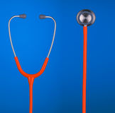 橙色在蓝色背景隔绝的听诊器耳机和响铃 库存照片