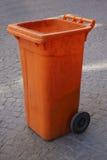 橙色塑料垃圾箱或自行车前轮离地平衡特技容器 图库摄影