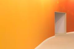 橙色墙壁和开放入口在一间空的现代屋子 库存图片