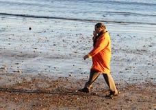 橙色外套的一名妇女走在海滩的在早期的春天在格洛斯特,马萨诸塞 库存图片