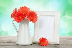 橙色大丁草花和照片框架在木桌上 免版税库存图片