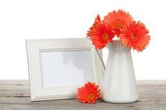 橙色大丁草花和照片框架在木桌上 免版税图库摄影