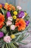橙色大丁草雏菊、紫罗兰色郁金香和桃红色玫瑰花束  免版税库存图片