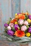 橙色大丁草雏菊、紫罗兰色郁金香和桃红色玫瑰花束  库存照片