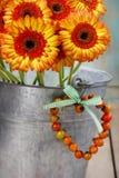 橙色大丁草雏菊花束在银色桶的 图库摄影