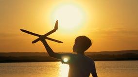 橙色天空和湖的背景的愉快的孩子在日落的夏天,使用与玩具飞机 影视素材