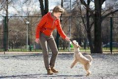 橙色夹克戏剧的女孩与小狗 免版税库存照片