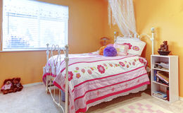 橙色女孩少年哄骗有玩具的卧室,白色床框架和 库存图片