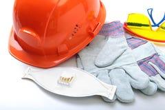 橙色安全帽、风镜、防毒面具、人工呼吸机和安全手套在白色背景 免版税图库摄影