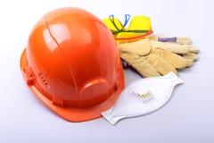 橙色安全帽、风镜、防毒面具、人工呼吸机和安全手套在白色背景 库存图片