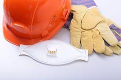 橙色安全帽、风镜、防毒面具、人工呼吸机和安全手套在白色背景 库存照片