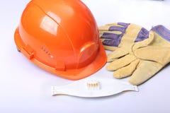 橙色安全帽、风镜、防毒面具、人工呼吸机和安全手套在白色背景 免版税库存图片