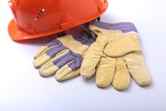 橙色安全帽、风镜和安全手套在白色背景 库存图片