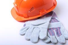 橙色安全帽、风镜和安全手套在白色背景 图库摄影