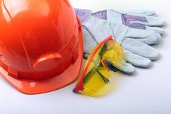 橙色安全帽、风镜和安全手套在白色背景 免版税库存图片