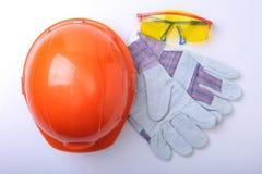 橙色安全帽、风镜和安全手套在白色背景 库存照片