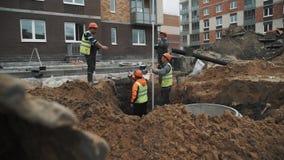 橙色安全帽的慢动作工作者谈话在垄沟在建筑工地 股票录像