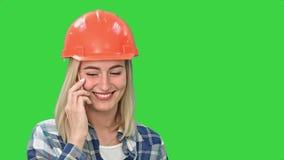 橙色安全帽的美丽的愉快的妇女有一个电话通过智能手机和微笑在一个绿色屏幕,色度钥匙上 影视素材
