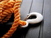 橙色尼龙把与金属拖曳勾子的绳索编成辫子 免版税库存照片