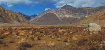 橙色山谷,秋天在喜马拉雅山:红色山,肮脏的植被,在蓝天的白色云彩 免版税图库摄影