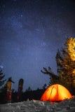 橙色帐篷和一个雪板在雪在背景满天星斗的天空 免版税库存图片