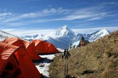 橙色帐篷在尼泊尔的山的背景中 免版税库存图片