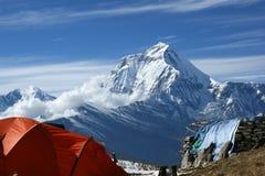 橙色帐篷在尼泊尔的山的背景中 库存图片