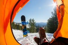 从橙色帐篷的看法在山、森林、雪板和太阳 库存图片