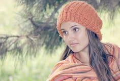 戴橙色帽子的年轻美丽的妇女 免版税库存图片