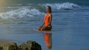 橙色开会的泡沫似的波浪洗涤女孩在沙子海滩 股票录像