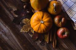 橙色微型南瓜、苹果和核桃在土气桌上与叶子 免版税库存照片