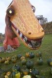 橙色恐龙注视同辈在南瓜Patchgoers 库存照片
