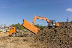 橙色挖掘机装载土地 免版税库存图片