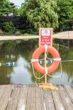 橙色救生圈和游泳责任自负在岗位签字在lak附近 免版税图库摄影