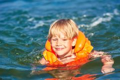 橙色救生背心游泳的小男孩在波浪海 免版税库存图片