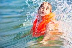 橙色救生背心游泳的小男孩在波浪海 图库摄影