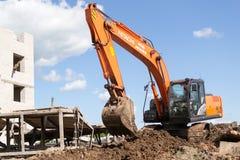 橙色日立挖掘机的移动的土壤 库存照片