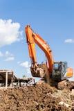 橙色日立挖掘机的移动的土壤 免版税库存照片