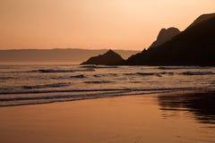 橙色日落前的光亮在Threecliff海湾, Gower湿沙子反射了  免版税库存照片