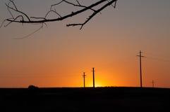 橙色日落和电定向塔 免版税库存图片