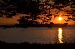 橙色日落小船和树 库存图片