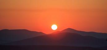 橙色日落的风景看法在山的 免版税库存图片