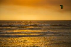 橙色日落的风筝冲浪者 库存照片