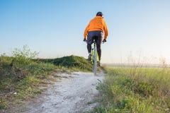 橙色有冠乌鸦的一个骑自行车者骑沿山道路的一辆自行车 极端体育的概念 库存图片
