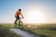 橙色有冠乌鸦的一个骑自行车者骑沿山道路的一辆自行车 极端体育的概念 免版税库存照片