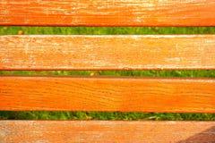 橙色木纹理和绿草背景 免版税图库摄影