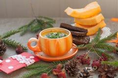 橙色杯子南瓜汤,几个新鲜的南瓜切片黑麦面包,片断和冬天在一个粗糙的克洛的装饰元素 免版税库存照片