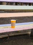 橙色杯子用在一个长木凳忘记的热的咖啡在春天公园 免版税图库摄影