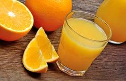 橙色果子用在一块玻璃的汁液在桌上 库存图片