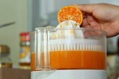 橙色果子紧压了用妇女手在榨汁器机器 图库摄影